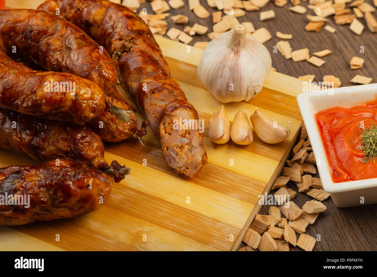 Homemade sausage on a wooden background with seasonings and sauce.