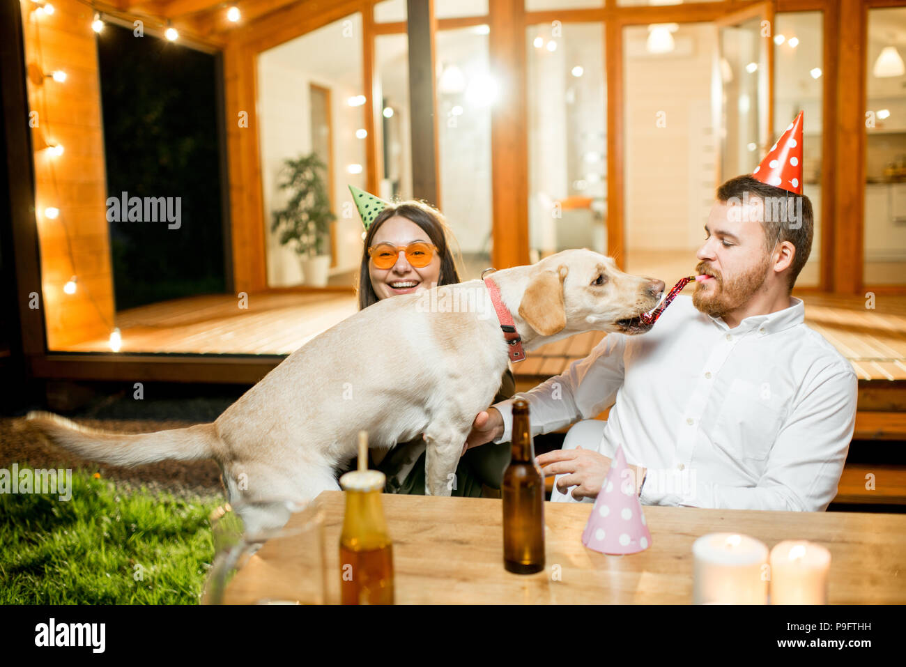 Dog with couple on the backyard of the house - Stock Image