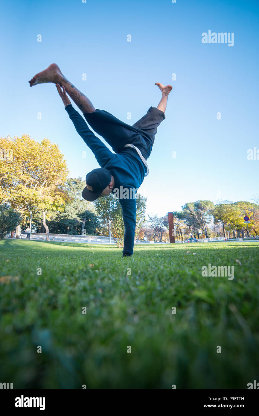 Young man doing handstand on grass in the street while doing parkour. - Stock Image