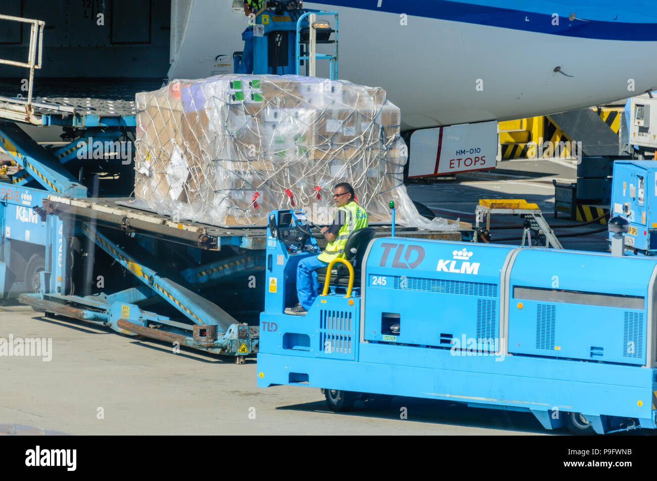 KLM ground crew load freight into the hold of a KLM Boeing 787-9 - Stock Image