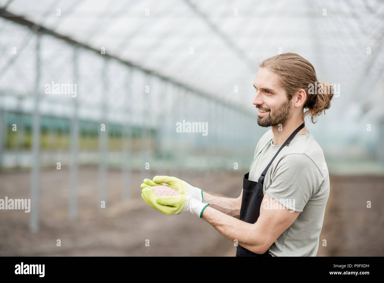 Farmer holding mineral fertilizers - Stock Image