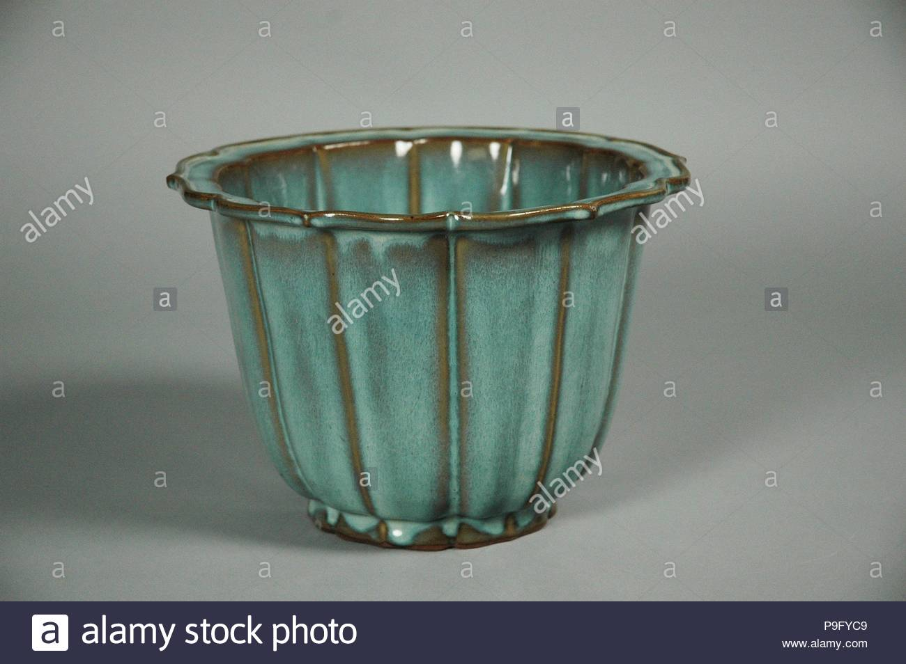 Flowerpot, Yuan (1271–1368)–Ming (1368–1644) dynasty, 14th–15th century, China, Stoneware with splashed glaze (Jun ware), H. 6 5/8 in. (16.8 cm); Diam. 9 1/2 in. (24.1 cm), Ceramics, Although no longer used at the court, Jun ware continued to be produced in the fourteenth and early fifteenth century. Most of the vessels made at this time were intended to hold flowers or bulbs, and many have numbers incised into their bases, possibly indications of size. - Stock Image