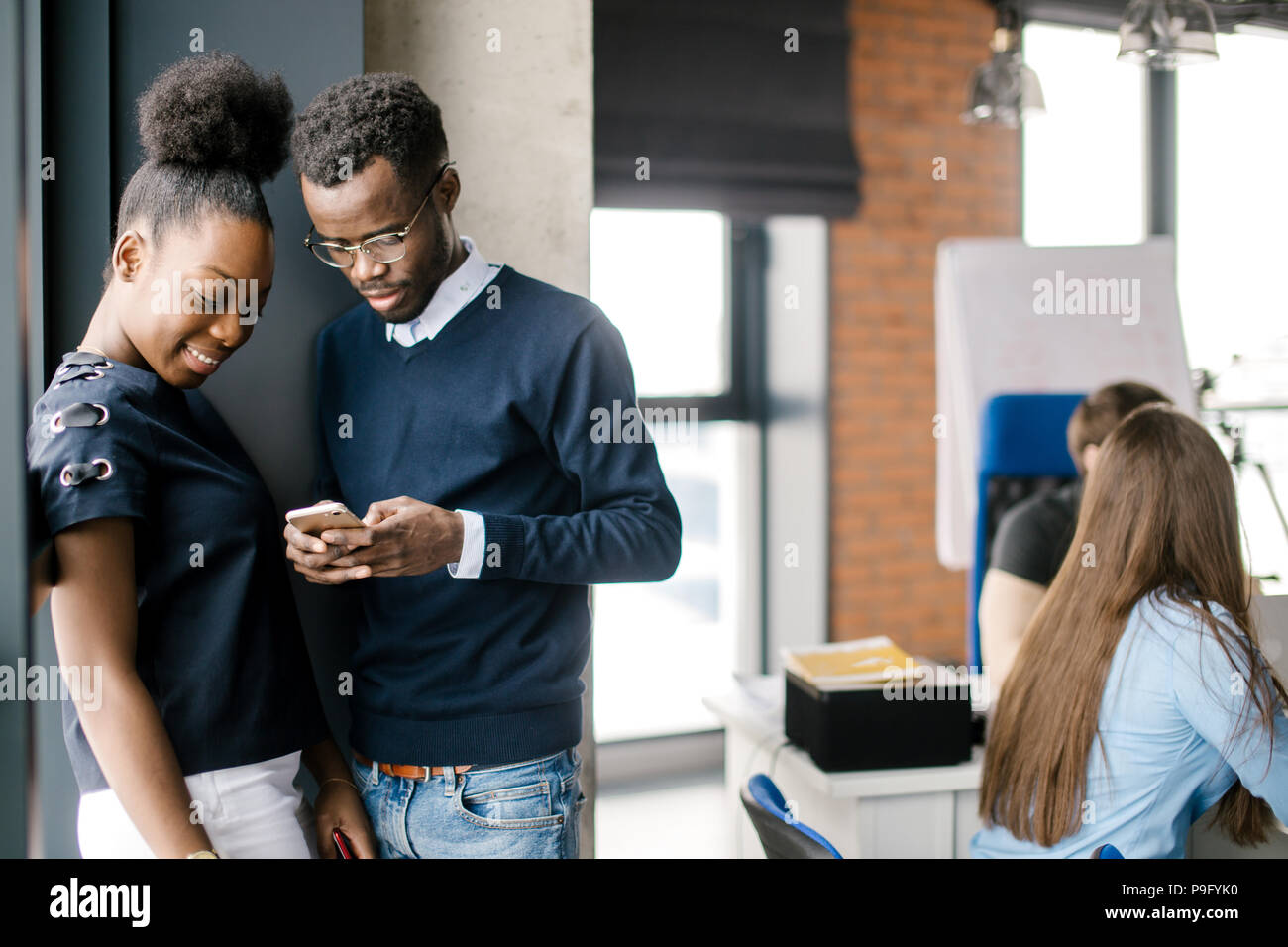 young african attractive woman and man standing in the corner of office and looking at the screen of cell phone in the loft office Stock Photo