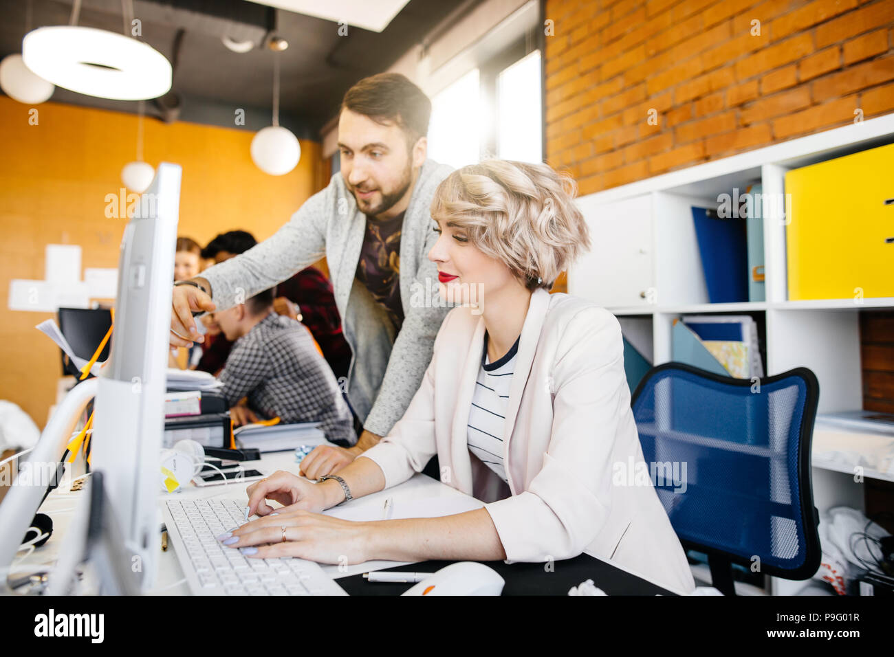 close up portrait of male assistant helping to beautiful manager to use computer in the loft office - Stock Image