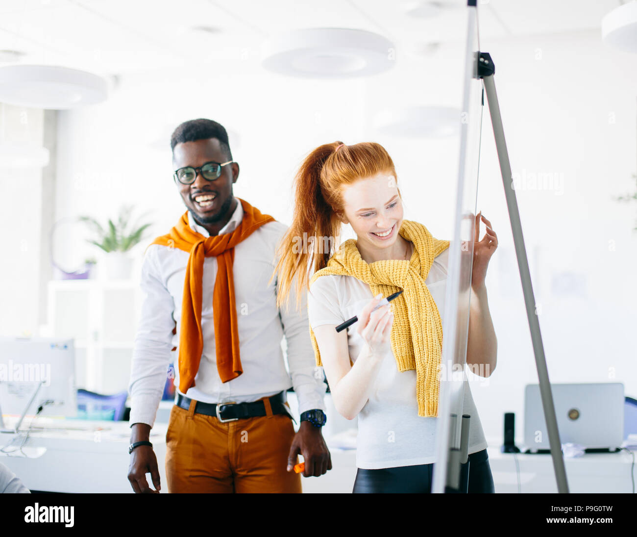 two artists drawing on flipchart in the modern studio - Stock Image