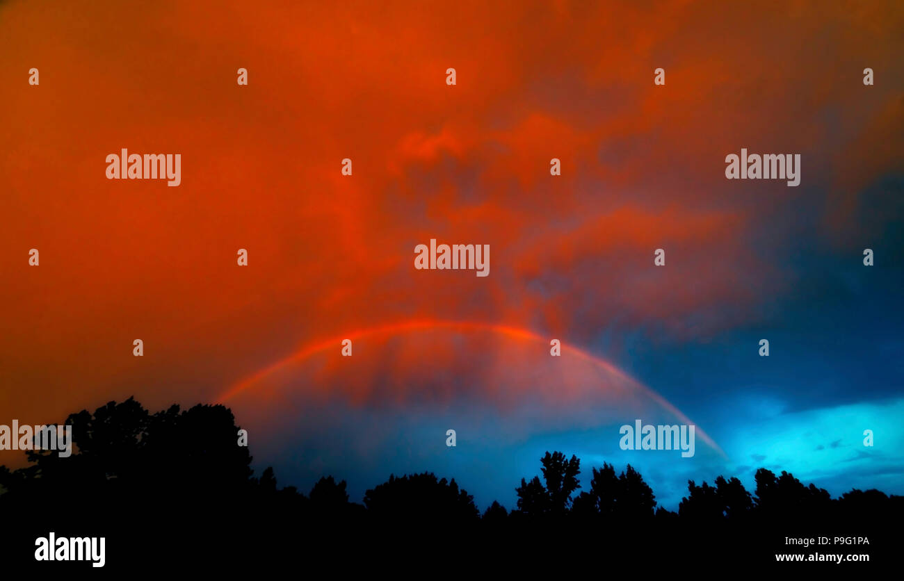 Storm clouds clearing, sun setting and a rainbow all at once. God is amazing! - Stock Image