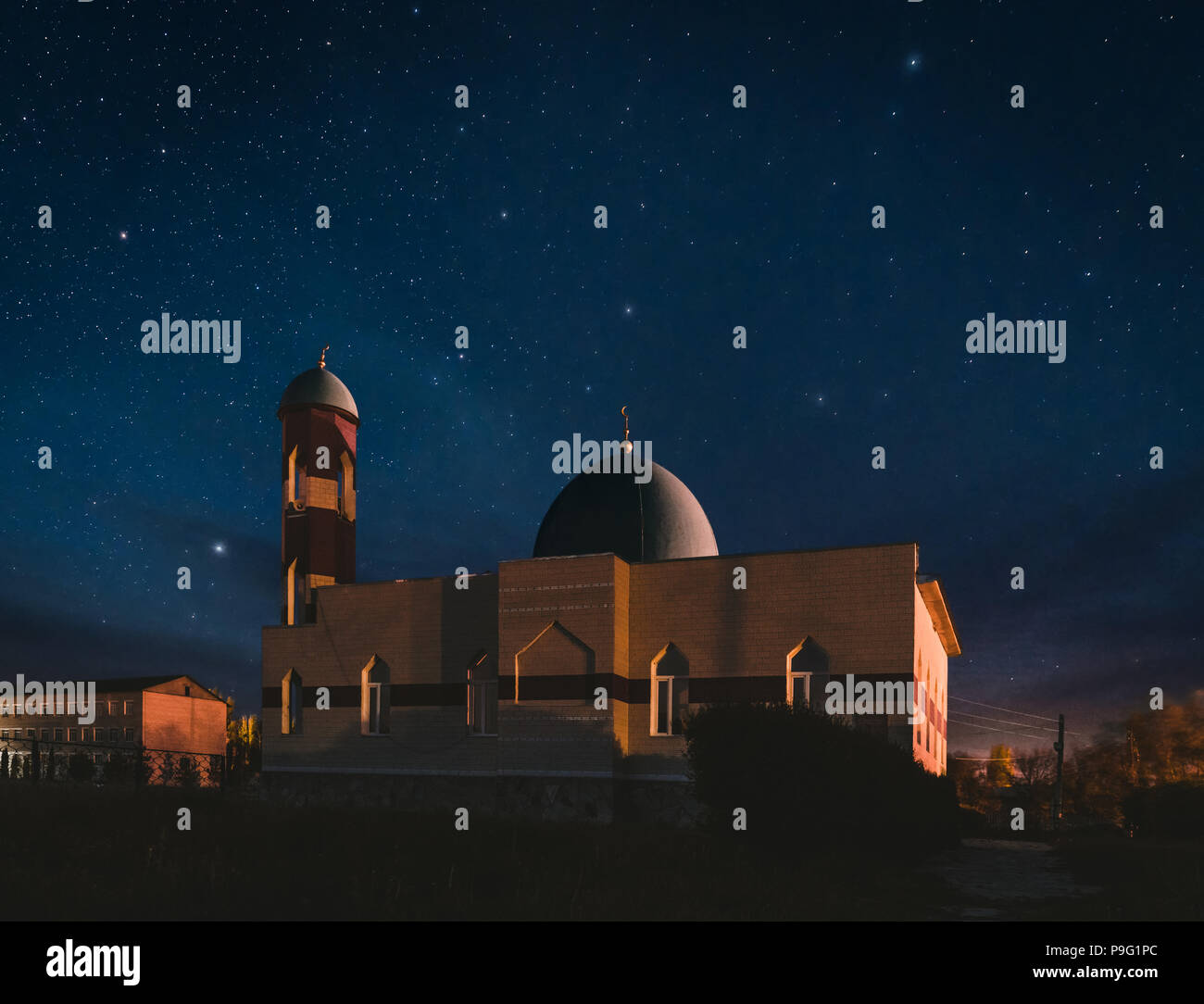 Illuminated Mosque at night time with fantastic sky and stars - Stock Image