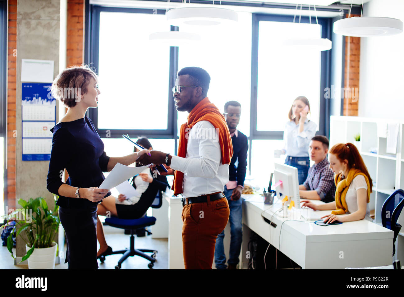 afro businessman and Caucasian businesswoman showing agreement. handshake among office workers - Stock Image