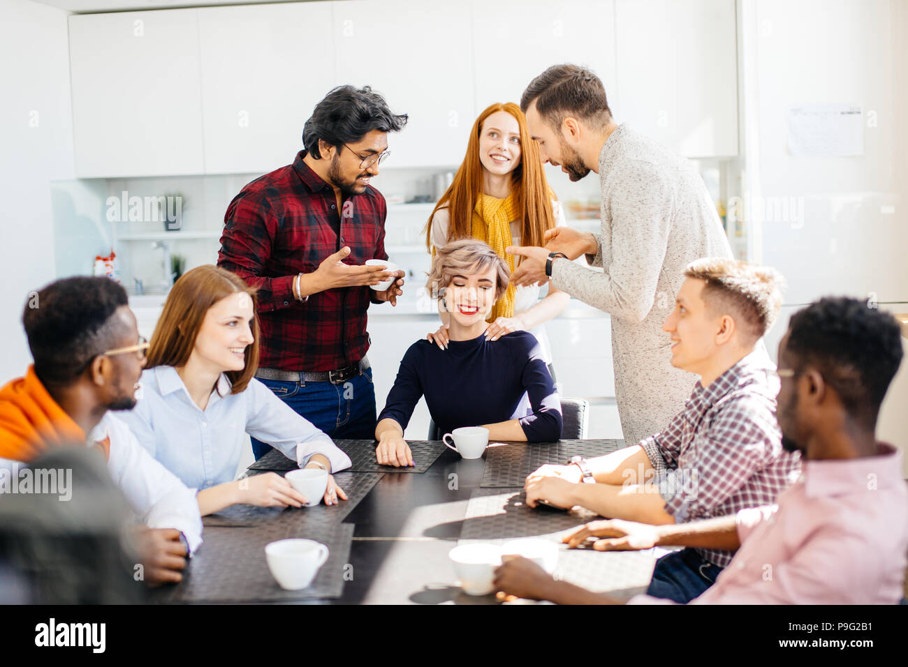 tide smiling female cheif with closed eyes is listening her workers complains. employees are persuading their leader in break time - Stock Image