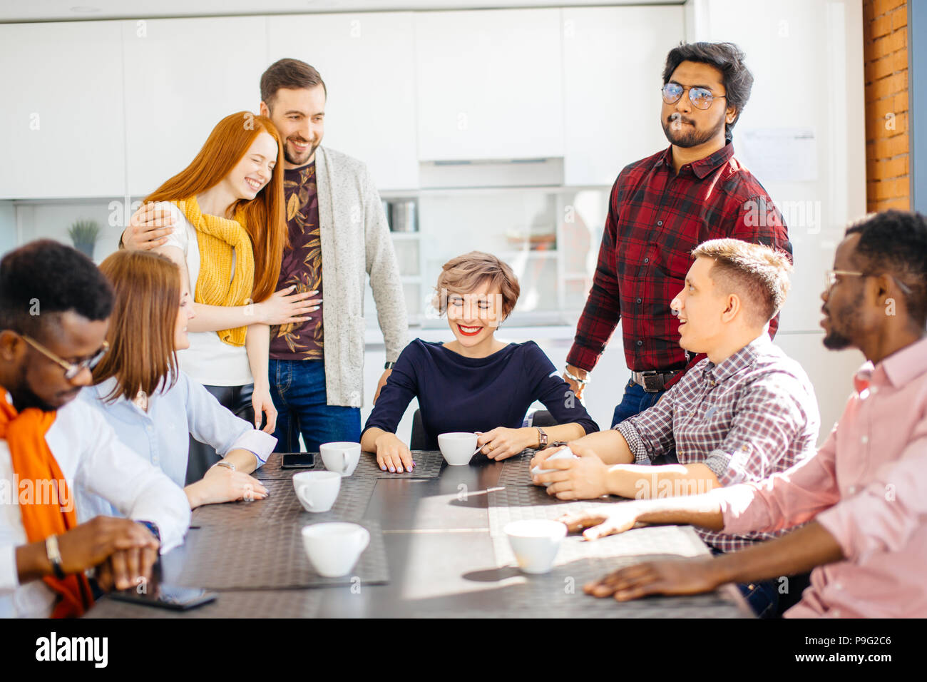 laughing business people telling jokes while drinking tea in the office kitchen - Stock Image