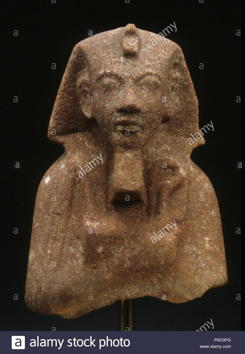 Funerary Figure of Akhenaten, New Kingdom, Amarna Period, Dynasty 18, ca. 1353–1336 B.C., From Egypt; Probably from Middle Egypt, Amarna (Akhetaten), Quartzite (red), h. 10.1 cm (4 in.), Although it lacks an inscription, this shabti is easily recognizable as Akhenaten. The nemes headcloth and the crook and flail shown on this example are more traditional shabti attributes than the khat headcloth and the ankh hieroglyphs found on other funerary figures of this king. - Stock Image