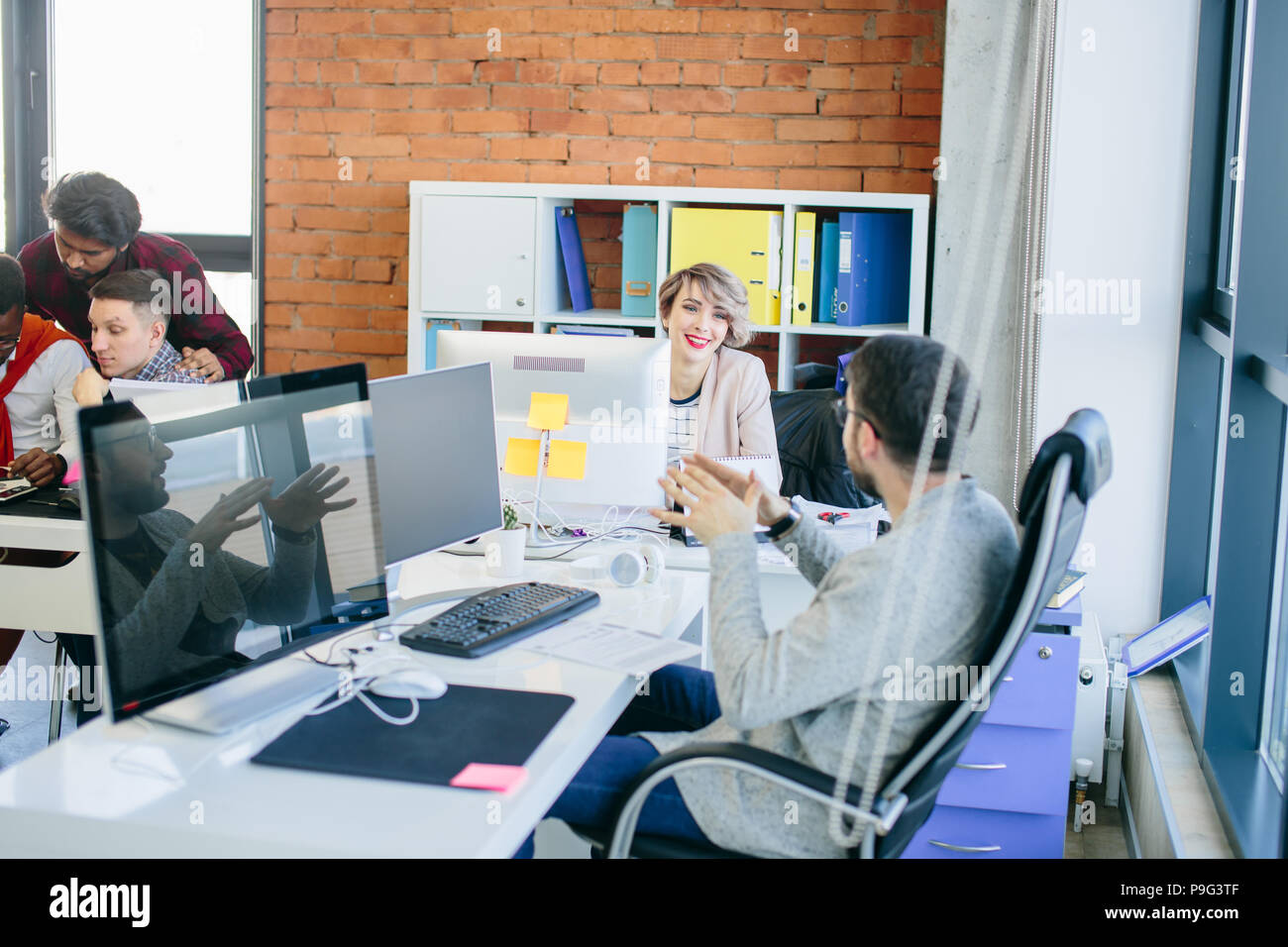 young good-looking team members discussing business ideas in loft office. - Stock Image