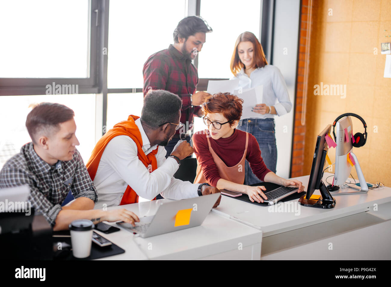 African man and pleasant red-haired woman are exchanging confidences at workplace among co-workers. closeup portrait - Stock Image