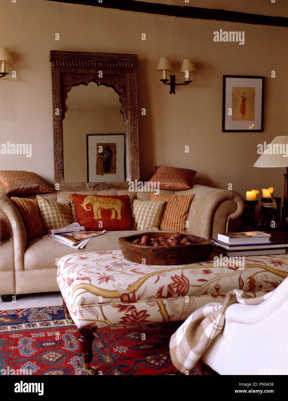 Carved Wooden Indian Mirror Above Beige Sofa With Patterned Cushions