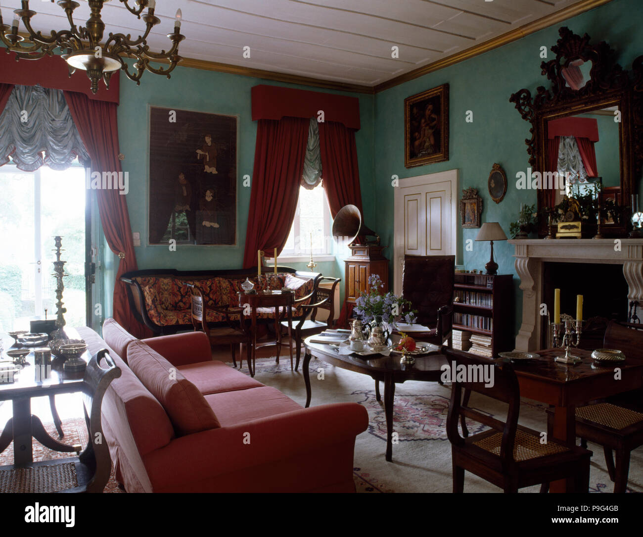 Pink Sofa And Antique Chairs And Small Tables In A Pale Turquoise Living  Room With Red Curtains On Windows