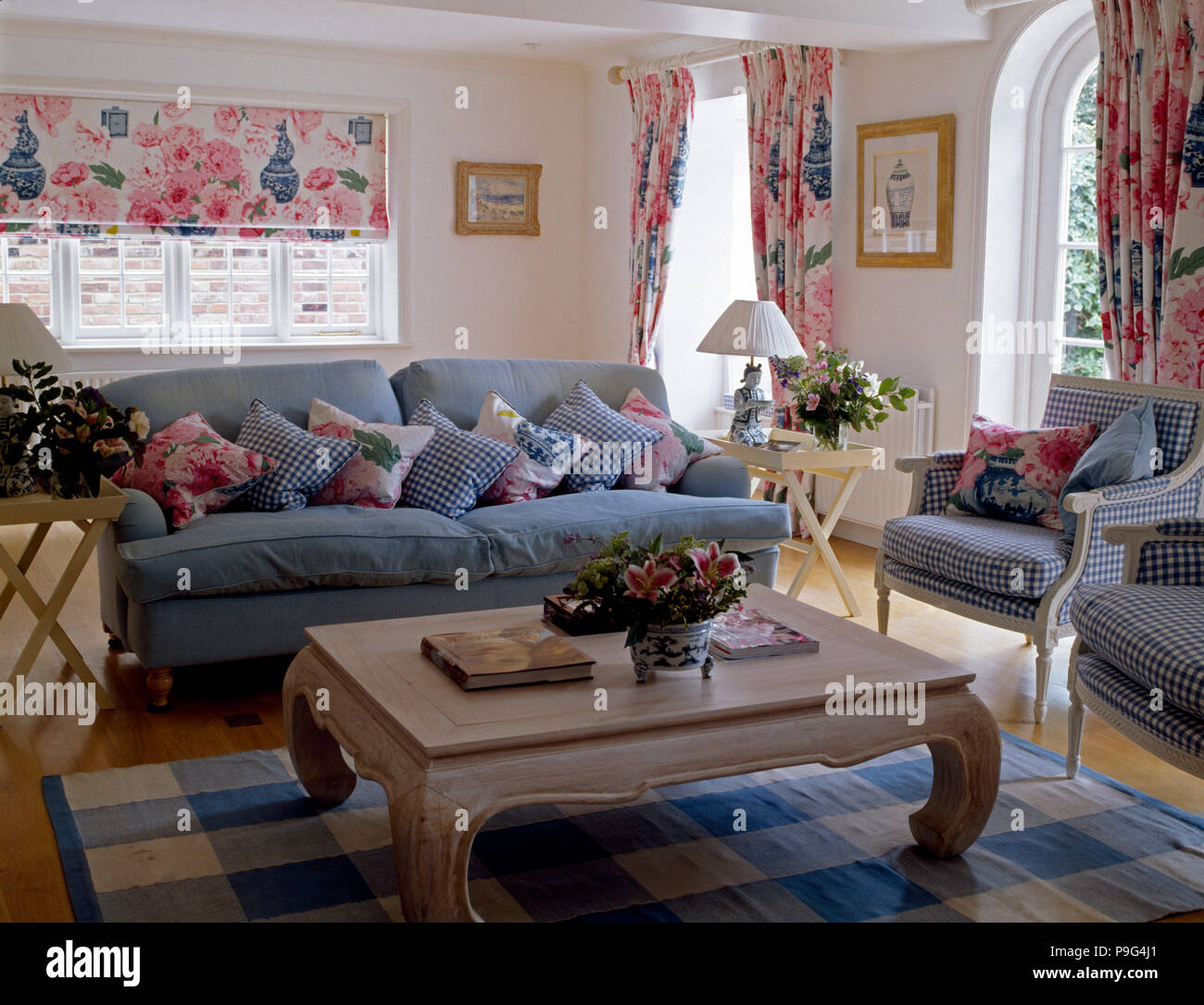 Attirant Lime Washed Coffee Table And A Blue Sofa Piled With Cushions In A Country  Living Room With A Pink Floral Blind