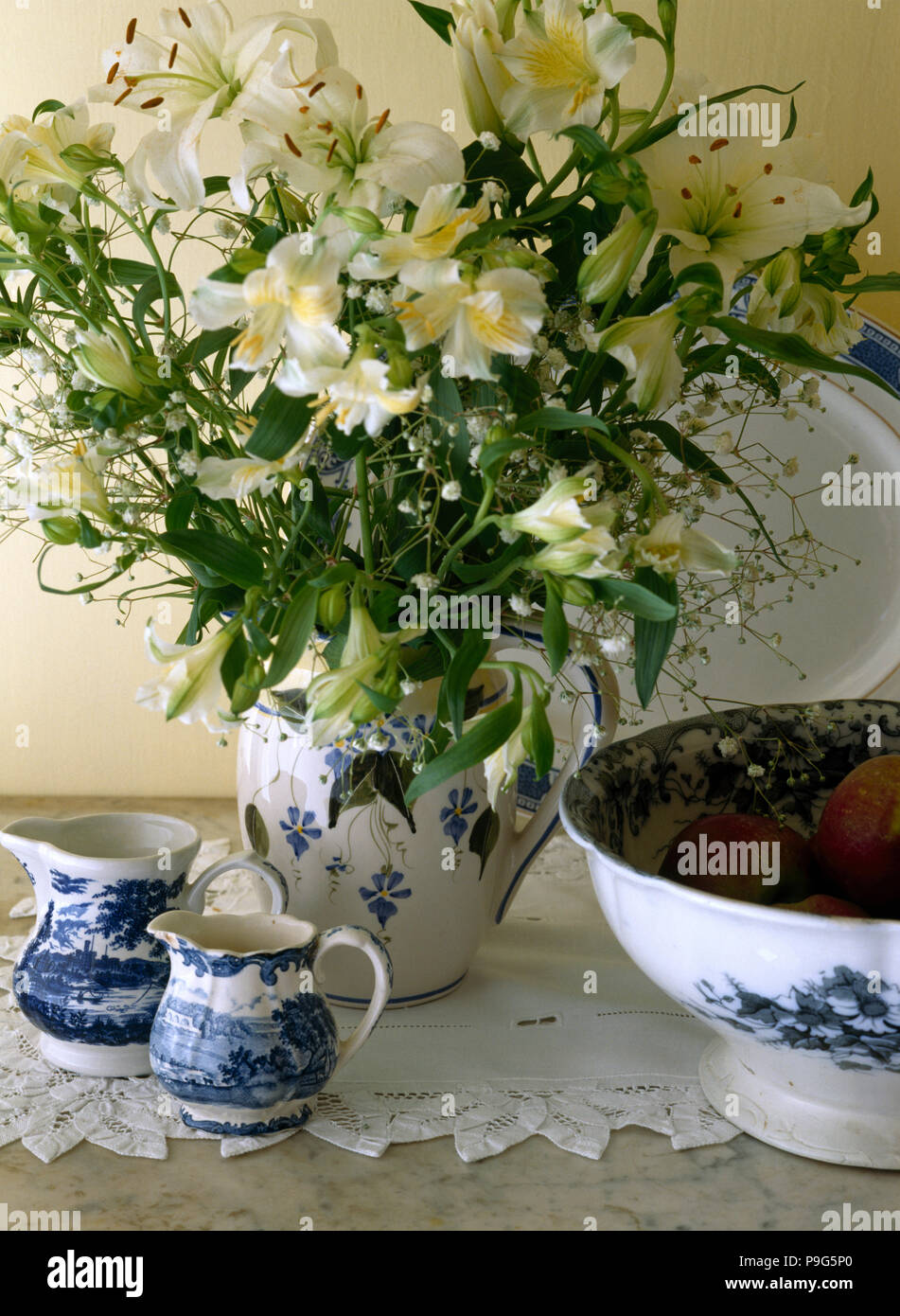 Cream Lilies In Old Blue Patterned Jug On Table With Small Blue And