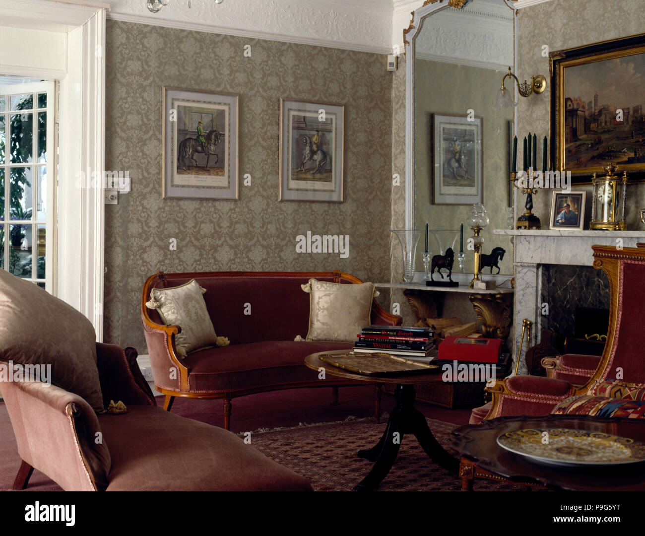 Velvet upholstered sofas in an old fashioned living room with pale grey wallpaper