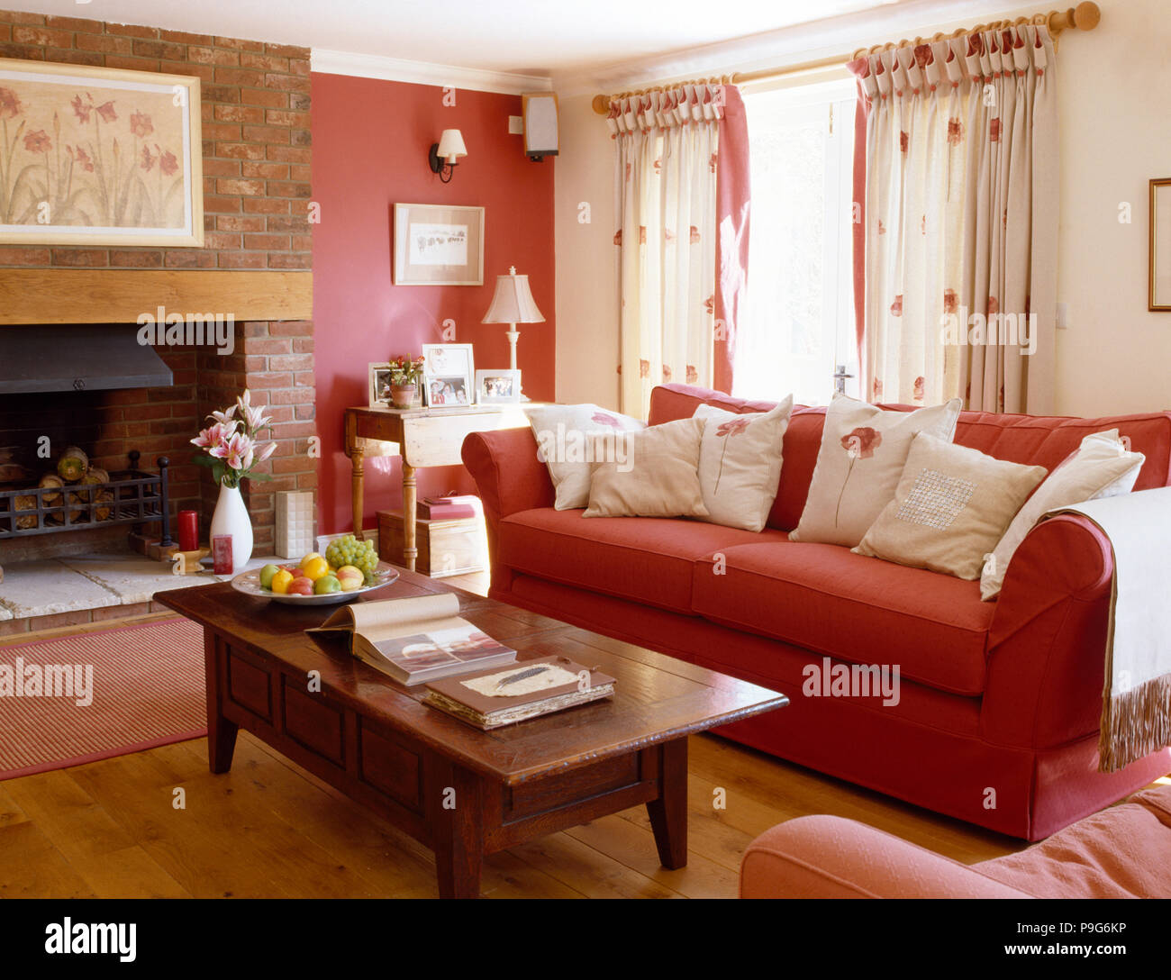Wooden coffee table and red sofa with white cushions in a - Red walls in living room ...