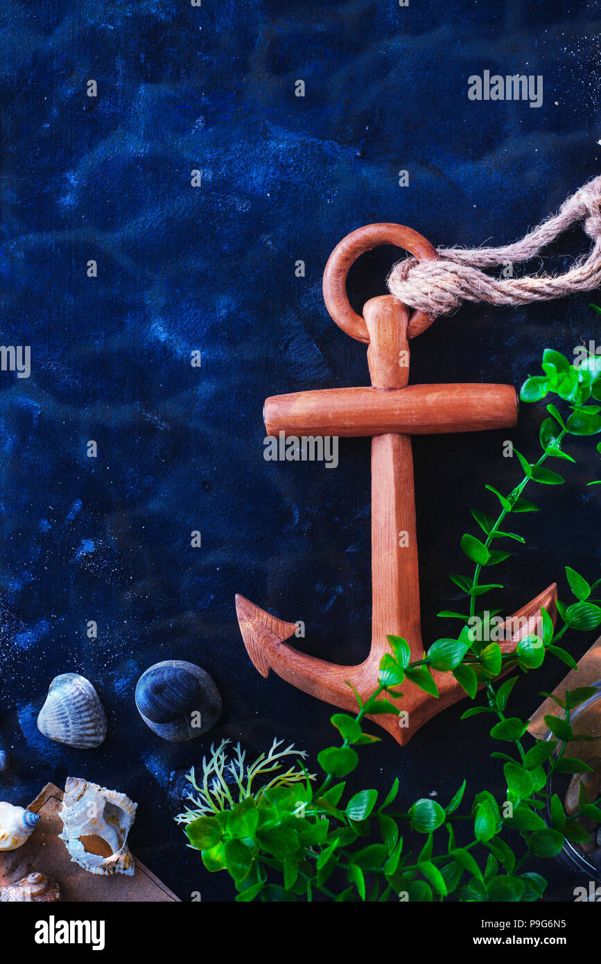 Anchor and seaweeds in an underwater still life on a dark background with water ripple. Sea travel and diving concept with copy space - Stock Image