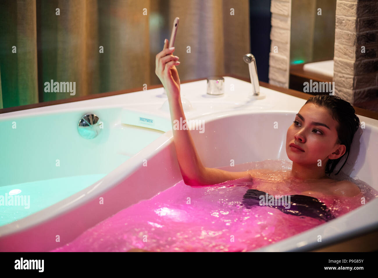 Woman having bath with color therapy and taking photo. taking selfy in the modern bath with light - Stock Image