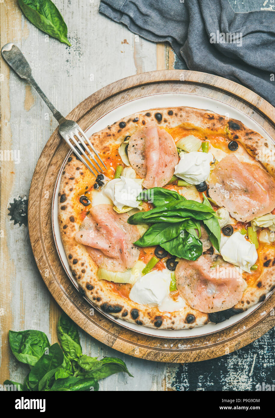 Freshly baked pizza with ham, artichokes, cheese and basil - Stock Image