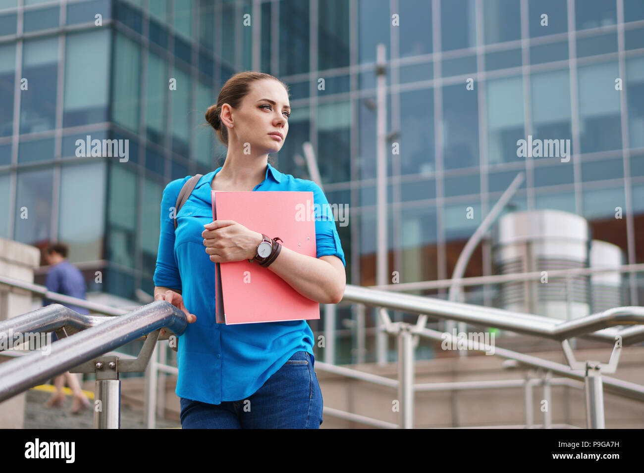 Young attractive girl is holding a folder for documents. The manager stands on the steps of the business center and looks thoughtfully sideways. - Stock Image