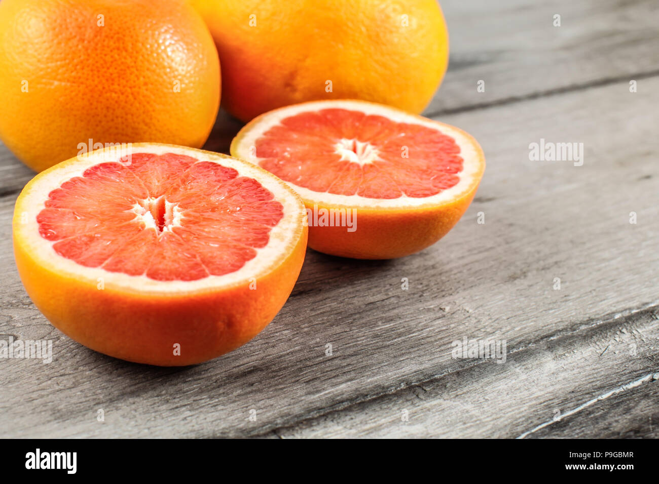 Pink red grapefruit cut in half, with two whole in background on gray wood table. - Stock Image