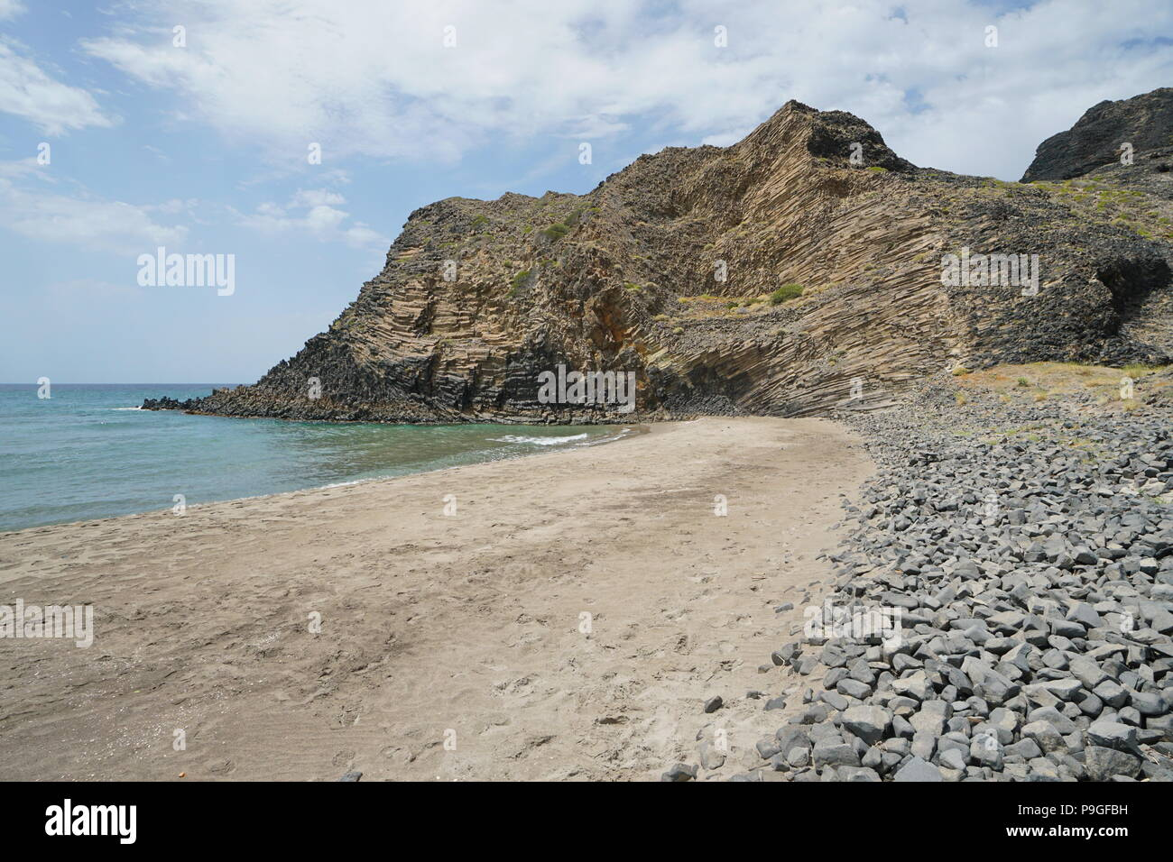 Sandy beach and volcanic rock formation on the coast in the Cabo de Gata-Níjar natural park, Mediterranean sea, Cala Grande, Almeria, Andalusia, Spain - Stock Image