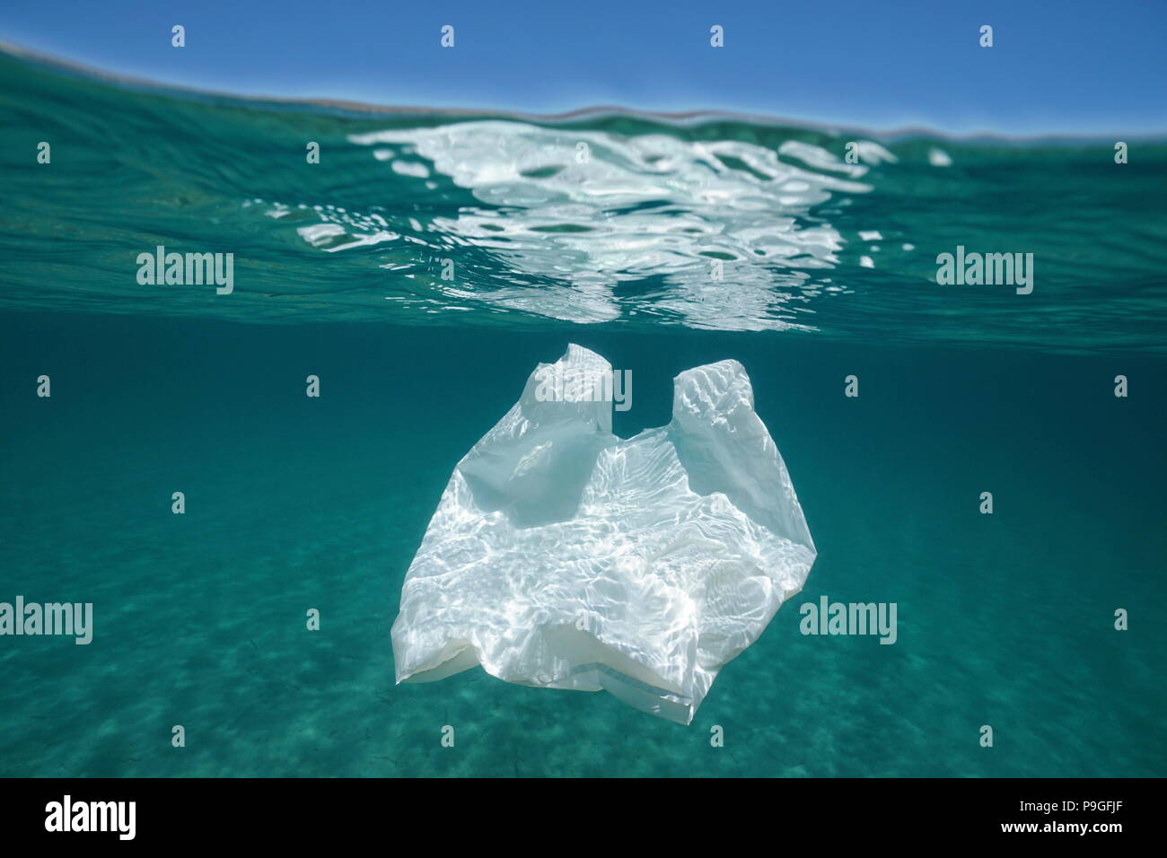 Underwater pollution a plastic bag adrift in the Mediterranean sea below water surface, Almeria, Andalusia, Spain - Stock Image