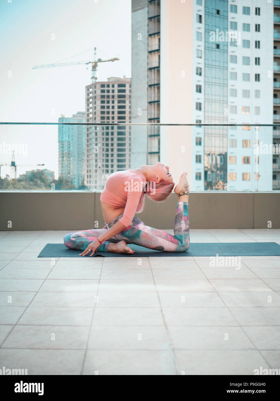Young slim woman with pink dyed hair doing yoga practice on terrace of modern city. Girl keeping fit and healthy body relaxing on rooftop during practice pose - Stock Image