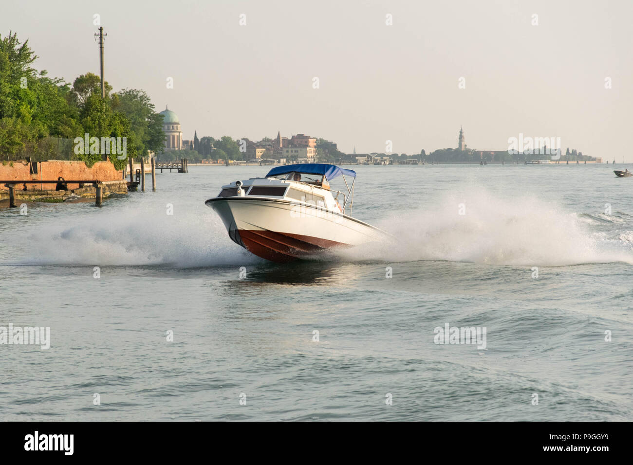 Europe, Italy, Veneto, Venice. Fast motorboat breaking waves. LagUne di Venezia nealr Lido di Venezia. Big water splash. - Stock Image