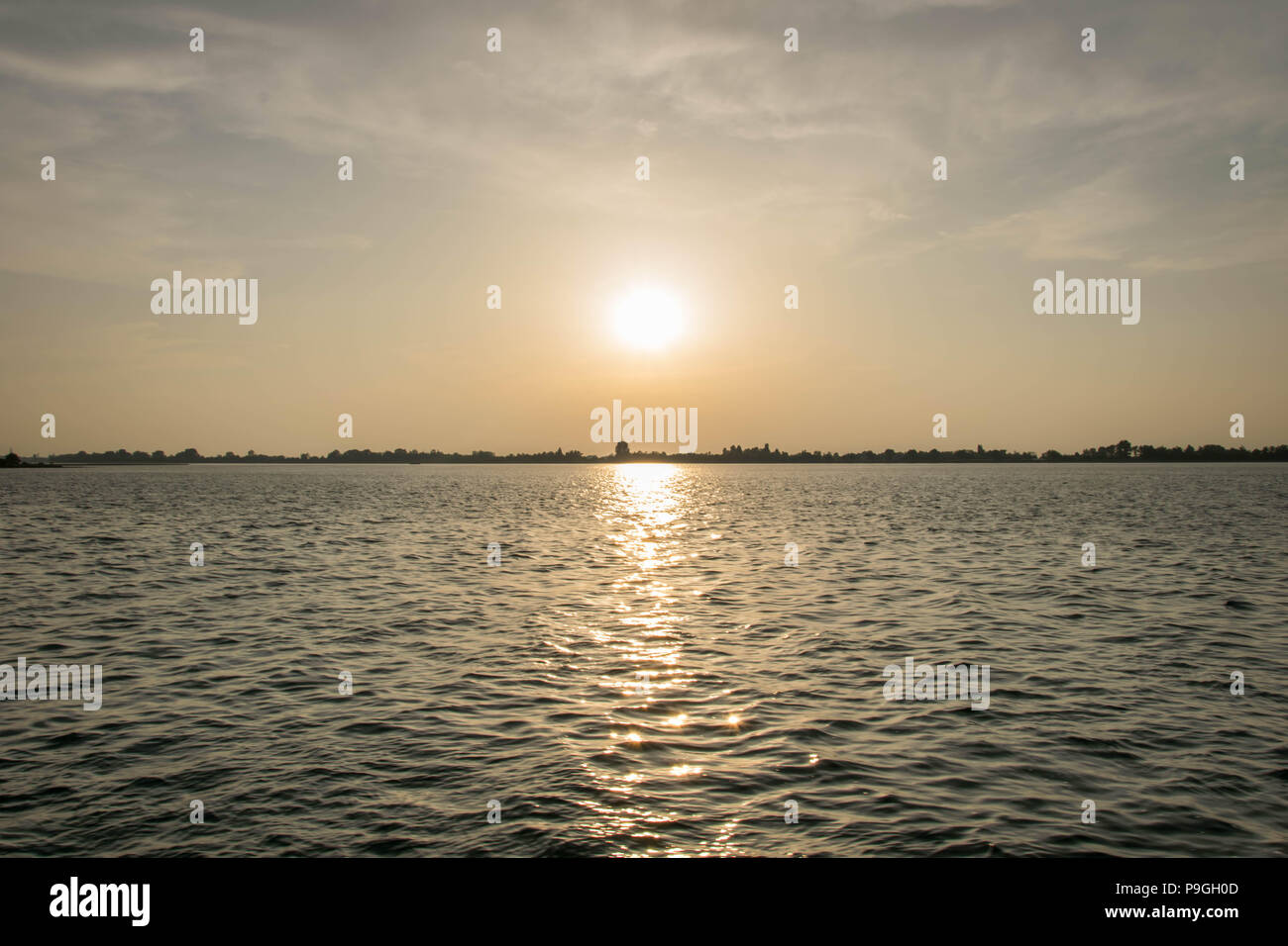 Europe, Italy, Veneto, Venice. Picturesque sunset over Lagune di Venezia (Venice Lagoon) seen from vaporetto (water tram) heading Punta Sabbioni. - Stock Image