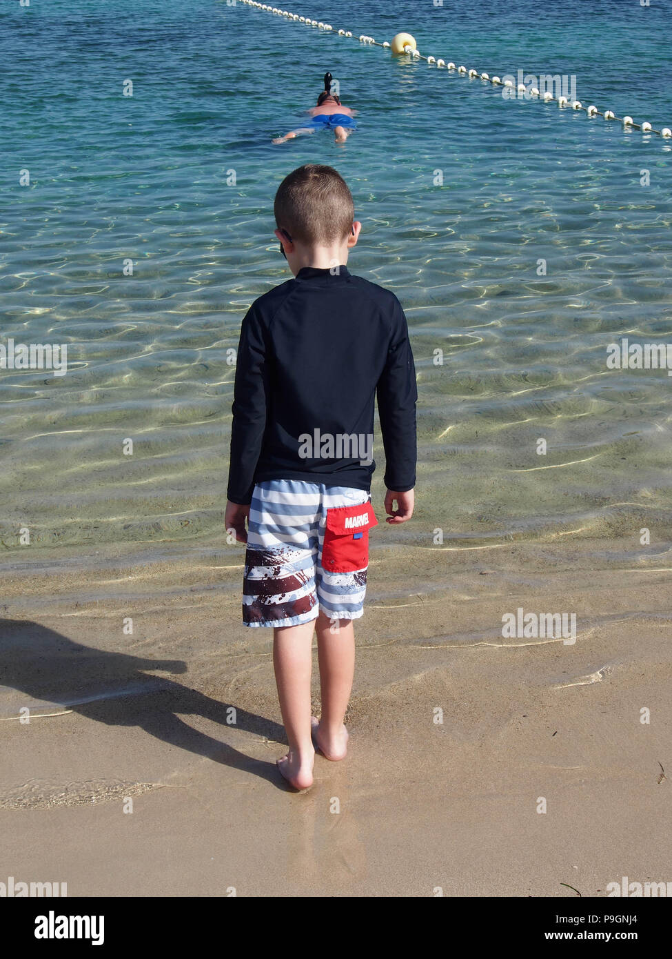 The back of a boy wearing a UV protective top on the beach - Stock Image