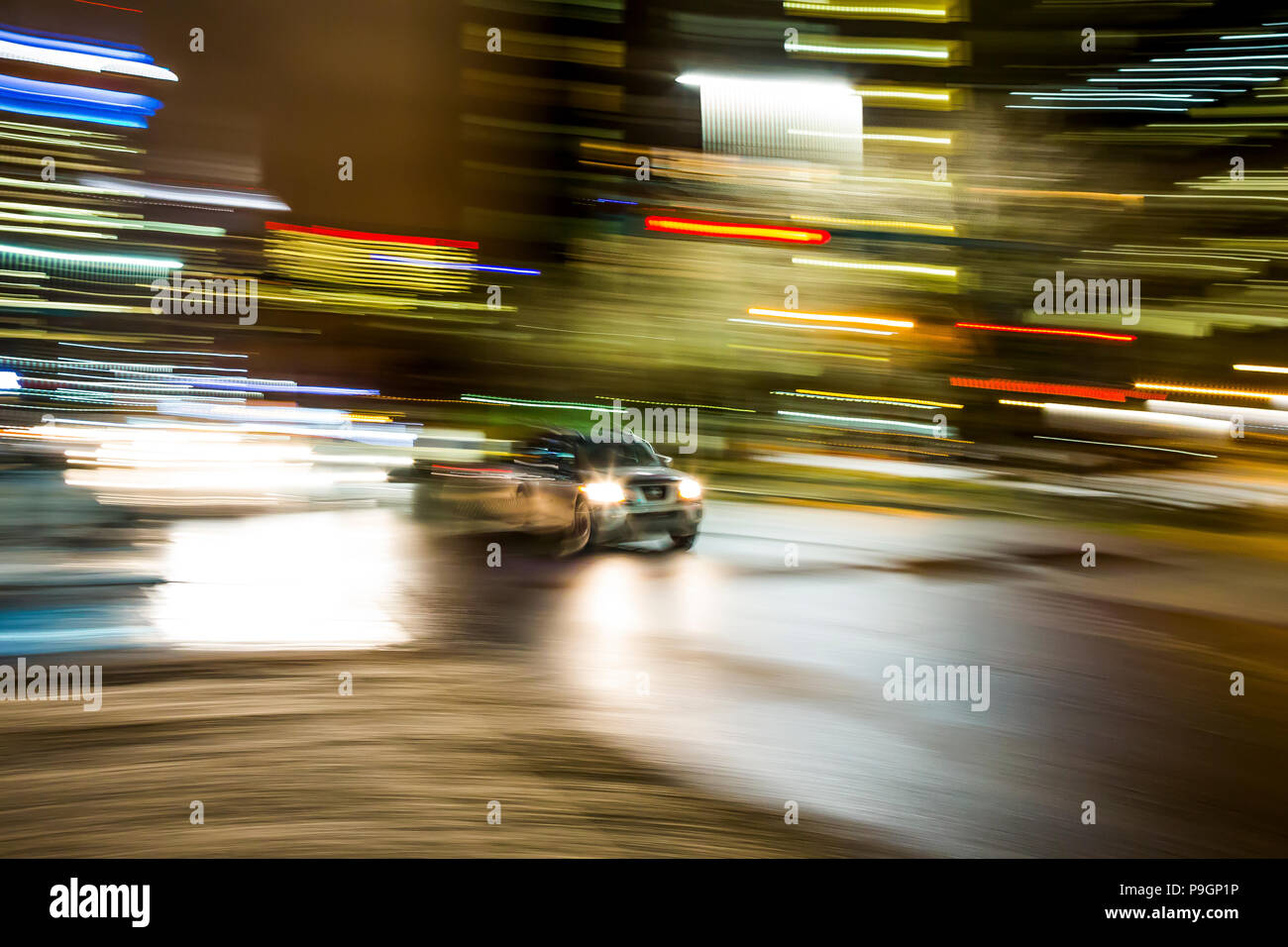 Motion blur as a vehicle drives through downtown Calgary at night. - Stock Image