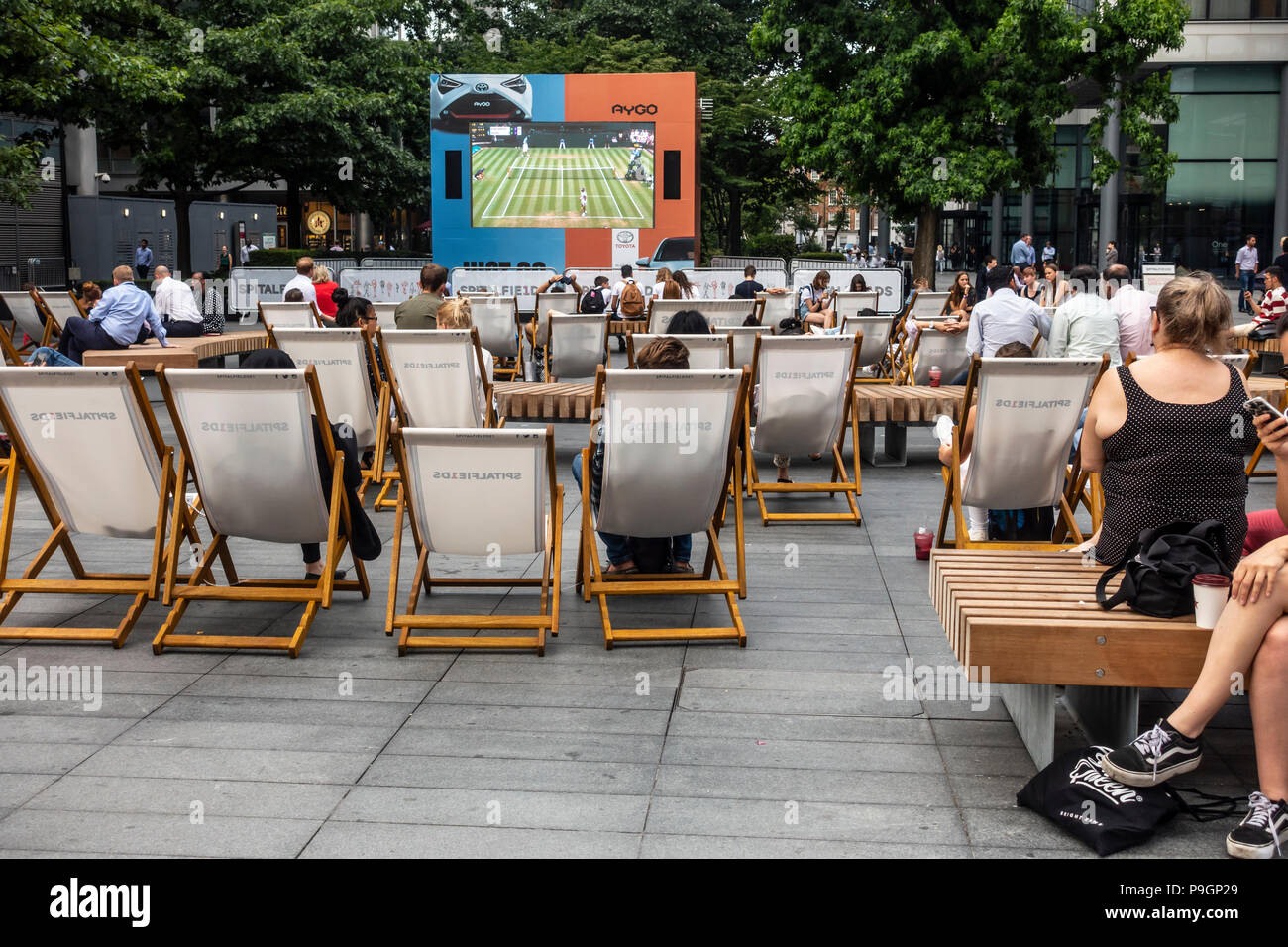 People relaxing, chatting and watching tennis from Wimbledon in Bishops Square, a privately-owned public space in Spitalfields, London. - Stock Image