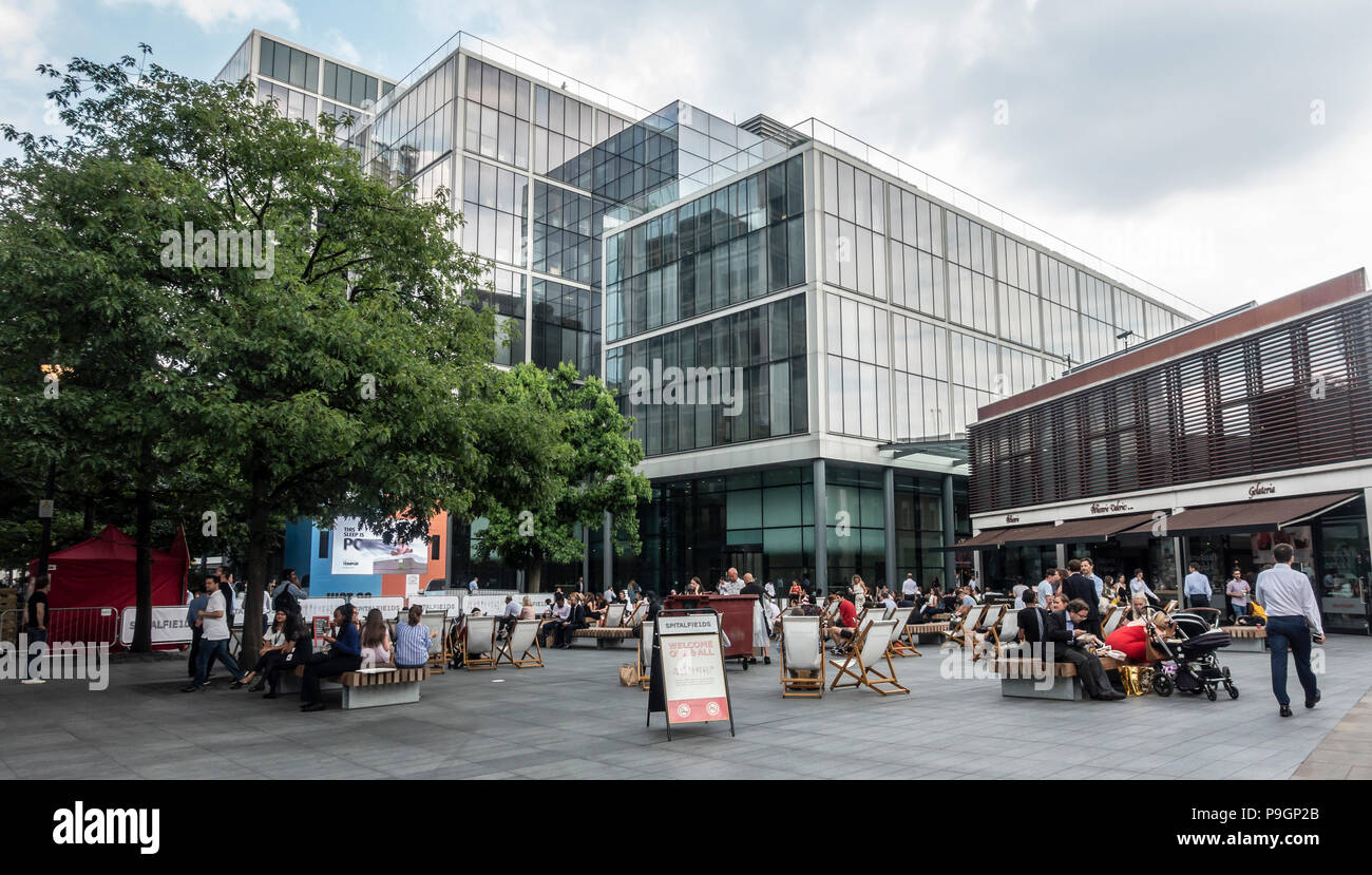 People relaxing on deckchairs or wooden benches chatting in Bishops Square, a privately-owned public space in Spitalfields London. Patisserie Valerie - Stock Image