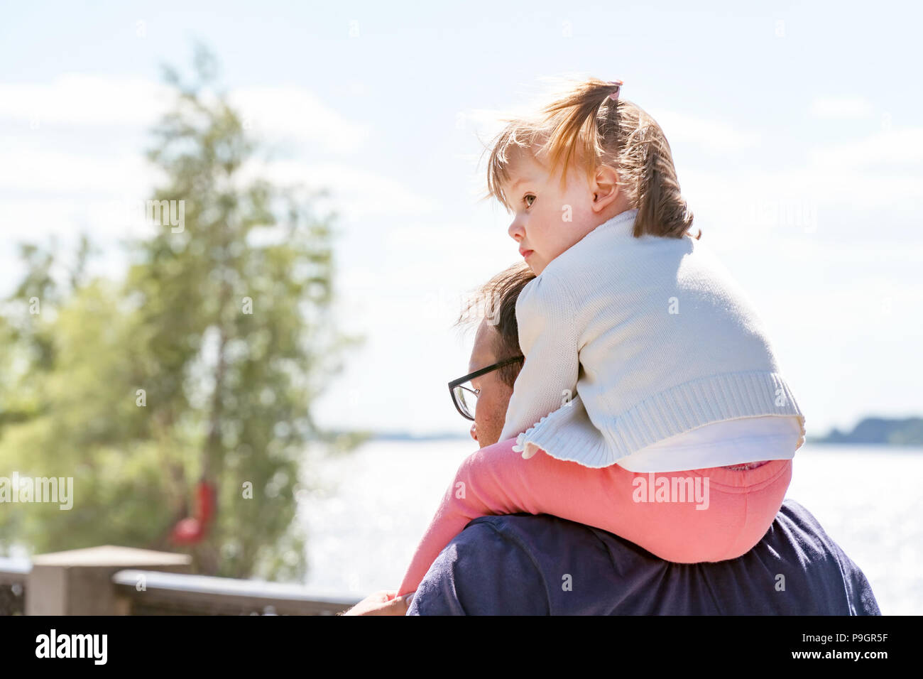 Little Girl sitting at the daddy on the neck - Stock Image