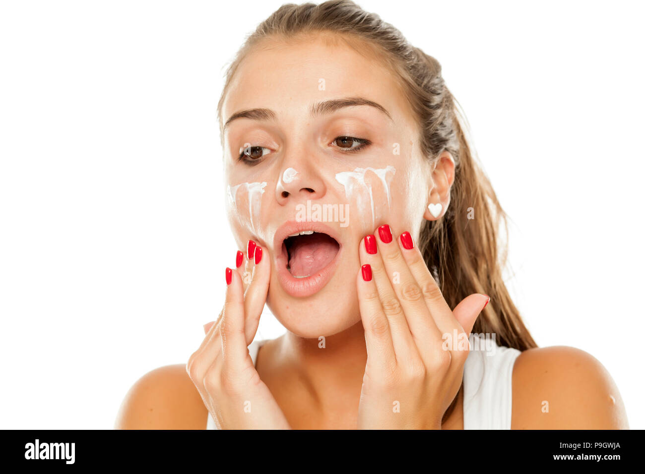 young woman applying cream to her face - Stock Image