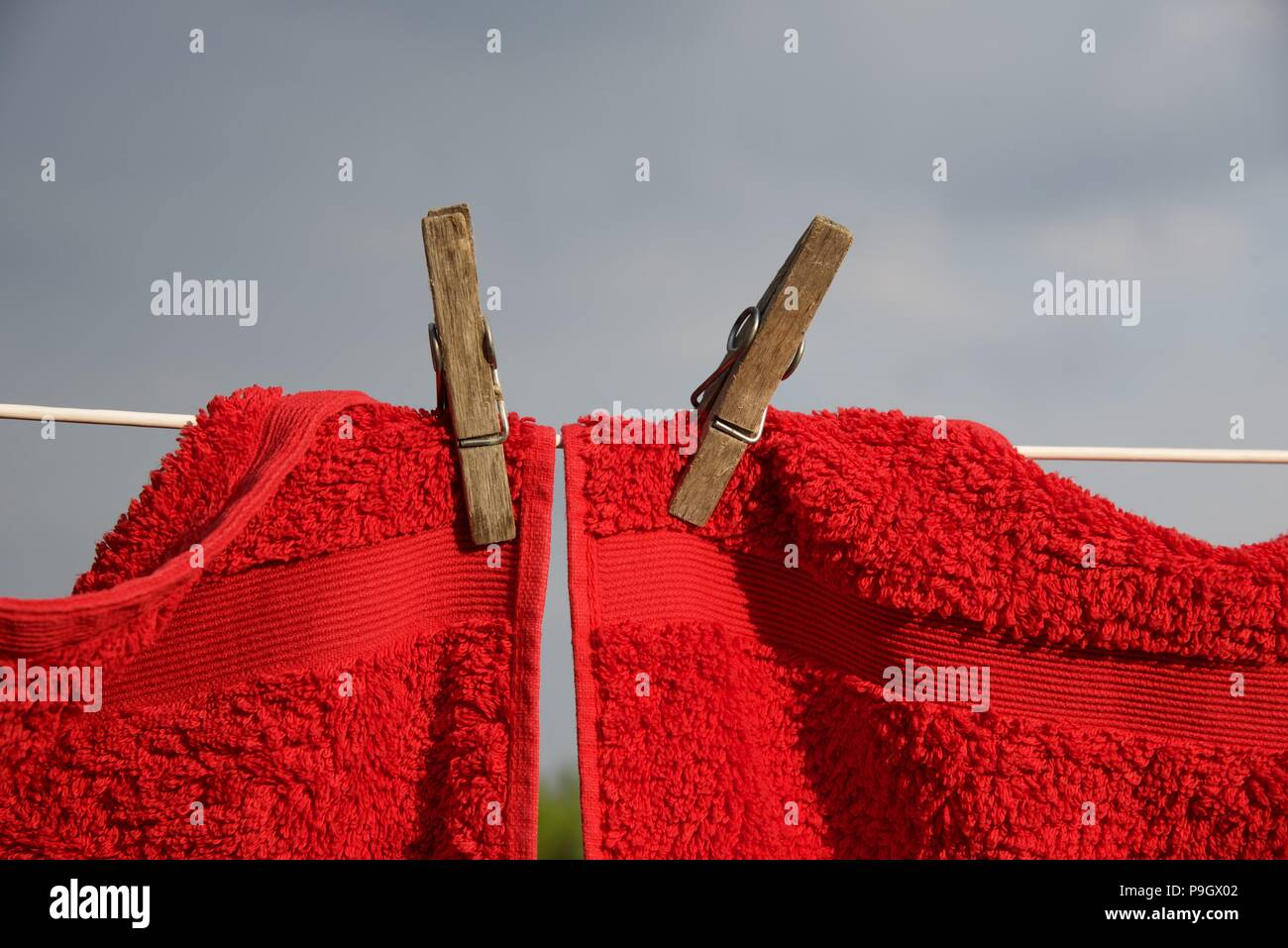 Washing line: red and grey towels hung with sprung wooden pegs on a white nylon coated washing line - Stock Image
