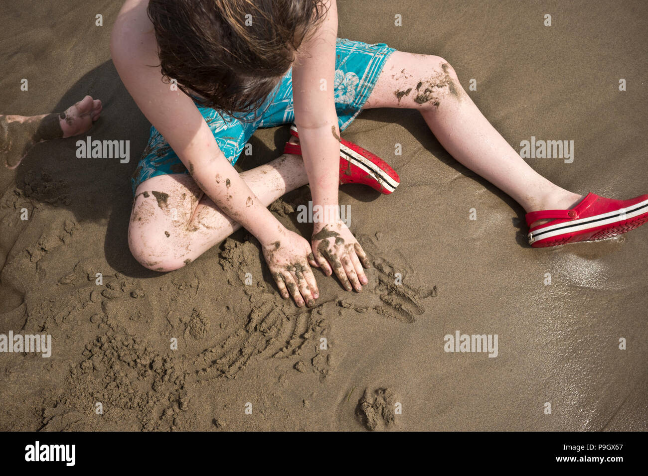 looking down at a ten year old boy sitting on a sandy beach playing with the sand with his hands - Stock Image