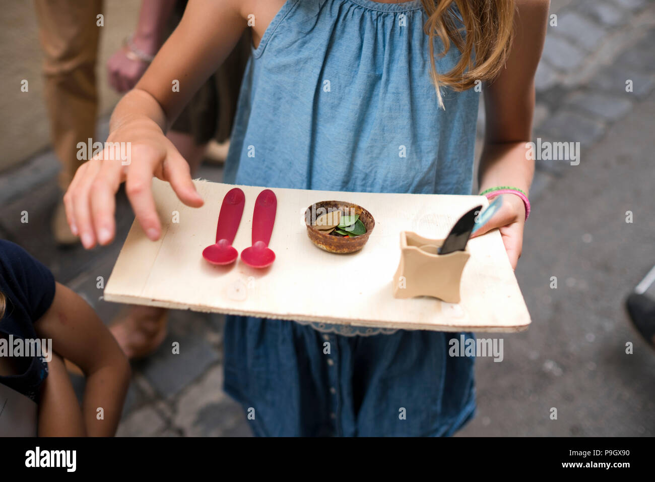 cropped frontal view of 6 year old girl holding up pretend meal tray made of a scrap of wood, displaying a rusty top full of leaves and two red spoons - Stock Image