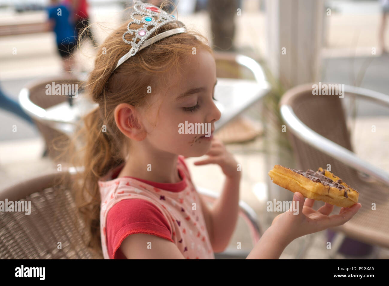 close up of a 4 year old girl with red long hair wearing a tiara, eating a waffle with nutella on a cafe terrace - Stock Image