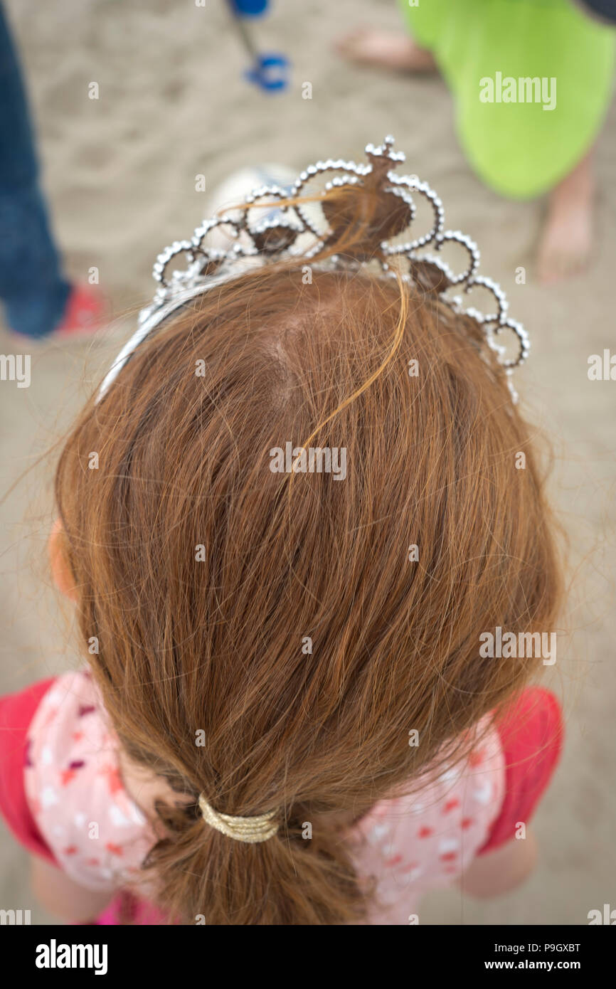close up of top of head of a 4 year old girl with red long hair wearing a tiara on a beach in France - Stock Image