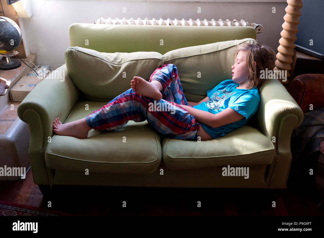 an eleven year old boy with long hair lies asleep in his pyjamas on a sofa in his home - Stock Image