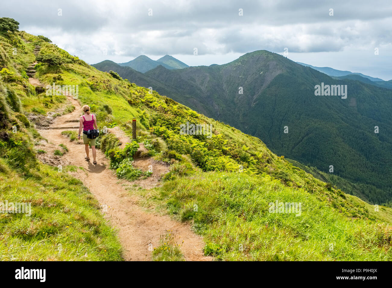 Female walker on The slopes of Pico da Vara, the highest point on Sao Miguel, Azores - Stock Image