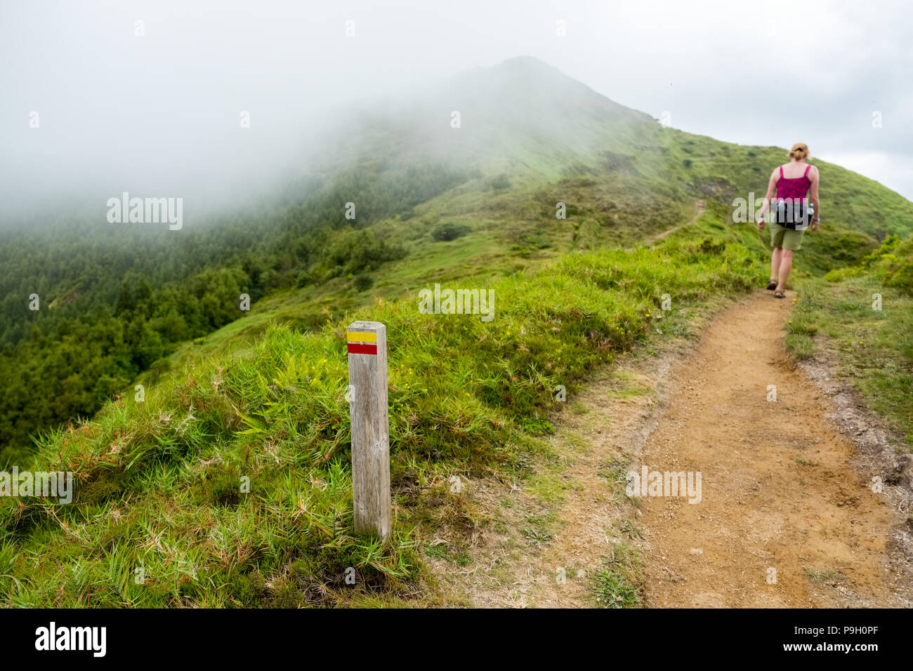 Female walker on trail on The slopes of Pico da Vara, the highest point on Sao Miguel, Azores - Stock Image