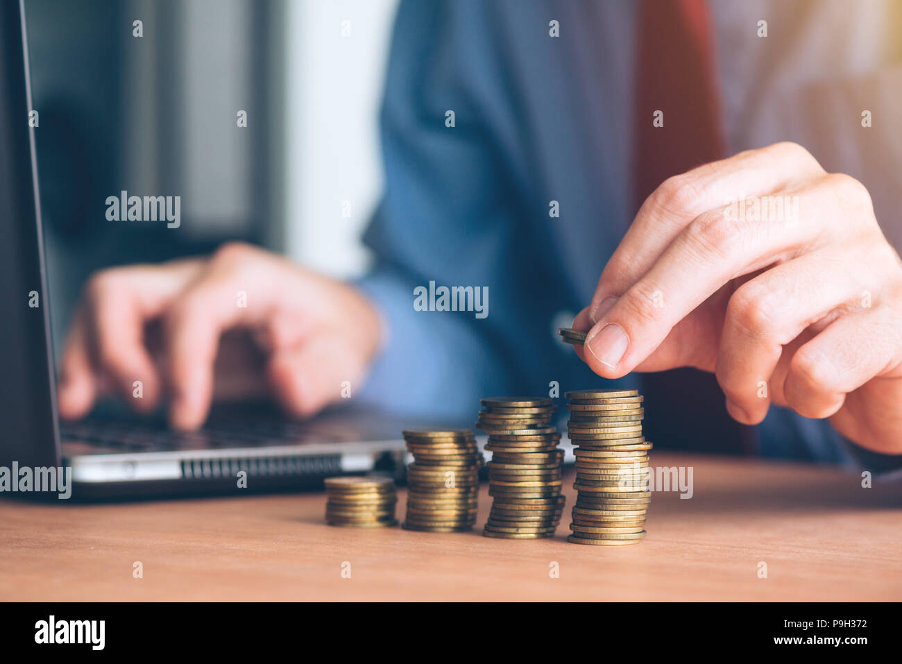 Finances and budgeting, businessman stacking coins on office desk - Stock Image