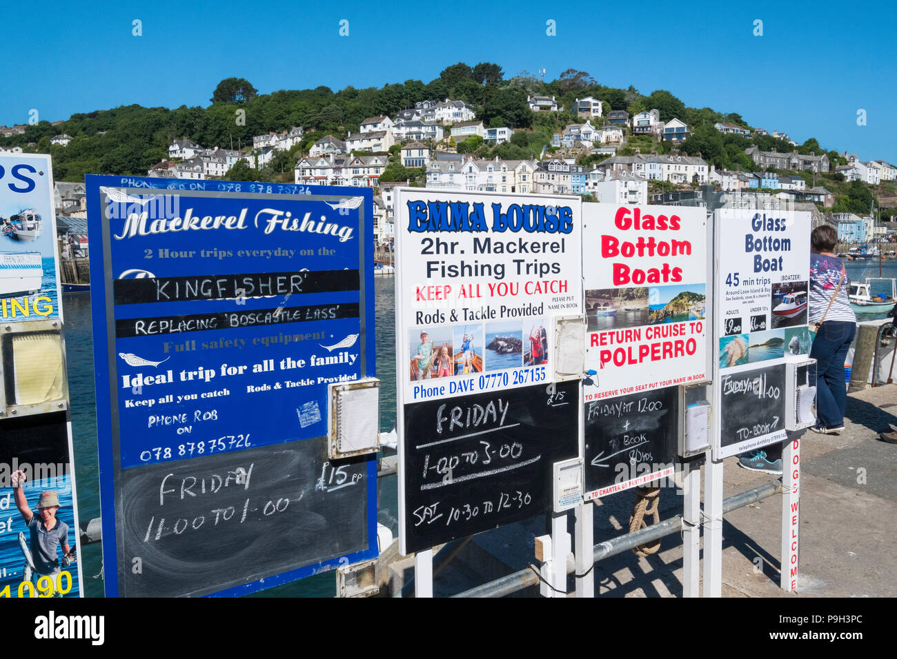 Signs advertising mackerel fishing and glass bottom boat trips in the fishing port of Looe, Cornwall, England, UK. - Stock Image