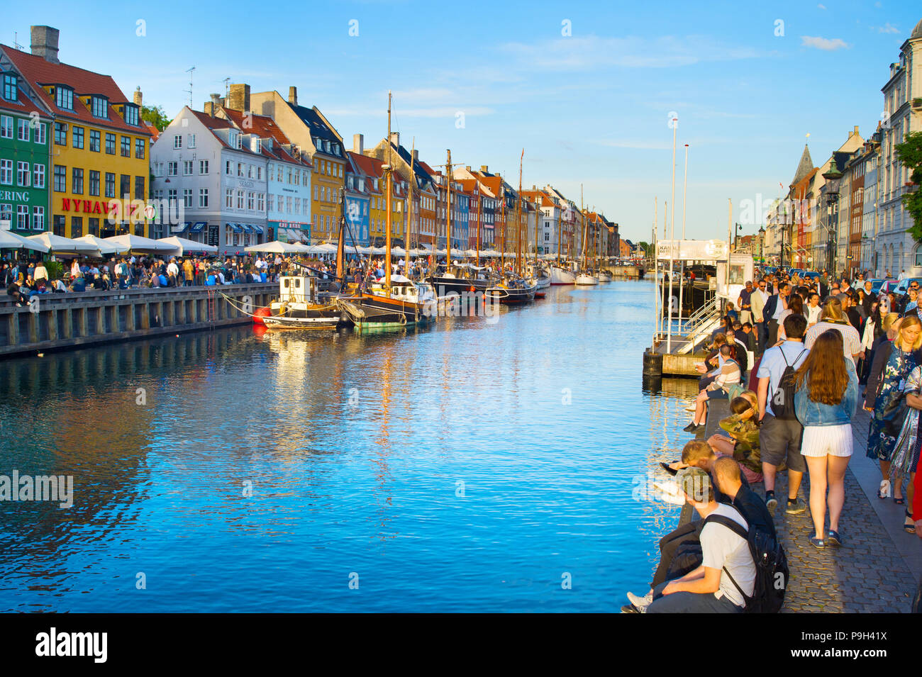 COPENHAGEN, DENMARK - JUNE 16, 2018: Tourists at Nyhavn district  - is one of the most famous landmark in Copenhagen - Stock Image